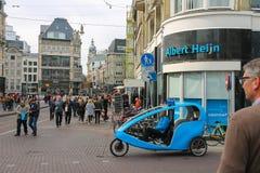 Turister som går i historisk stadsmitt av Amsterdam Royaltyfria Bilder