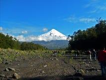 Turister som går in mot chilensk stor vulcano arkivfoton