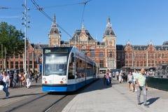 Turister som går nära en spårvagn i Amsterdam Arkivfoton