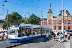 Turister som går nära en spårvagn i Amsterdam Arkivbilder