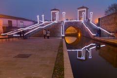 Turister som går på bron Trepponti, Comacchio, Italien vid natt Arkivbild
