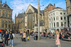 Turister som går på fördämningen, kvadrerar i Amsterdam, Nederländerna Royaltyfri Foto