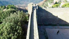 Turister som går på omkretsväggen av fästningen av Montalcino i 4k stock video