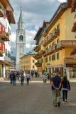 Turister som går till och med den huvudsakliga gatan i Cortina d'Ampezzo arkivbilder
