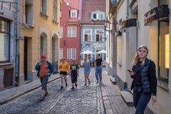 Turister som går upp en smal gata av Riga den gamla staden royaltyfria foton