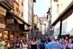 Turister som går vid Ponten Vecchio i Florence Arkivfoto