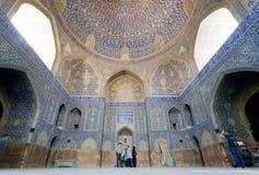 Turister som håller ögonen på stora konstverk med tegelplattor av den historiska persiska moskén Arkivbilder