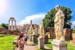 Turister som håller sig ögonen på och statyerna av oskulder nära huset av vestalsna, Roman Forum royaltyfri foto