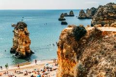 Turister som har gyckel i vatten, kopplar av och solbadar i den Lagos staden på stranden på havet av Portugal Arkivbilder