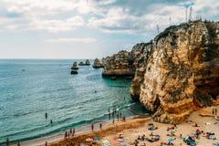 Turister som har gyckel i vatten, kopplar av och solbadar i den Lagos staden på stranden på havet av Portugal Arkivfoton