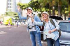 Turister som kallar taxien Fotografering för Bildbyråer