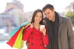 Turister som konsulterar hållande shoppingpåsar för telefon i vinter fotografering för bildbyråer