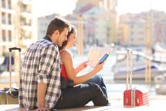 Turister som kontrollerar översikten och den smarta telefonen på ferie fotografering för bildbyråer