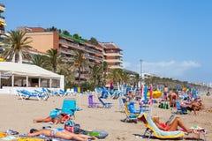 Turister som kopplar av på den sandiga stranden i Spanien Arkivfoto