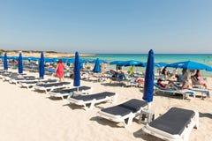 Turister som kopplar av på sunbeds på en sandig strand under strandumbrel Royaltyfri Bild