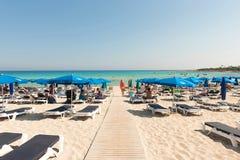 Turister som kopplar av på sunbeds på en sandig strand under strandumbrel Arkivbilder
