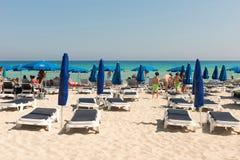 Turister som kopplar av på sunbeds på en sandig strand under strandumbrel Arkivfoton