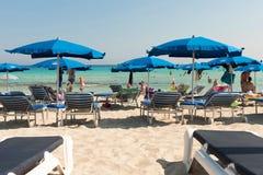 Turister som kopplar av på sunbeds på en sandig strand under strandumbrel Arkivbild