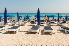Turister som kopplar av på sunbeds på en sandig strand under strandumbrel Royaltyfria Foton