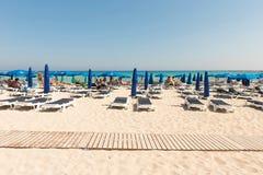 Turister som kopplar av på sunbeds på en sandig strand under strandumbrel Royaltyfri Fotografi