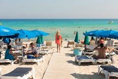 Turister som kopplar av på sunbeds på en sandig strand under strandumbrel Royaltyfria Bilder