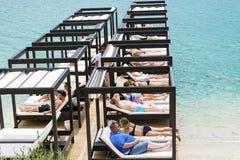 Turister som lägger på lyxiga sunbeds på stranden i ett hotell, tillgriper i Bodrum, Turkiet Fotografering för Bildbyråer