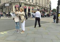 Turister som läser den pappers- översikten på den London gatan Arkivfoto