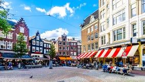 Turister som samlar på den Spui Plein Spui fyrkanten som omges av historiska hus med utsmyckade gavlar i mitten av Amsterdam royaltyfri foto