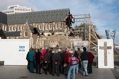 Turister som ser ar, fördärvar av den Christchurch domkyrkan Arkivfoto