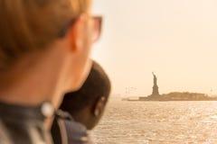 Turister som ser statyn av frihetkonturn i solnedgången från färjan för statenö, New York City, USA royaltyfria foton