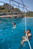 Turister som simmar i havet som är hållande på till repet som går yachten Royaltyfri Bild