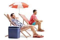 Turister som sitter i solstolar Arkivfoto