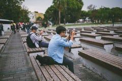 turister som sitter på bänkar med katten och tar foto vid kameror Royaltyfri Foto