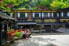 Turister som sitter på växtkrukan på gatan med stången, lokala byggnader och sikt av färgrika blomma blommor och gräsplanträd på  Arkivbild