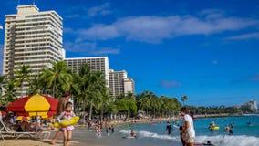 Turister som solbadar och surfar på den Waikiki stranden stock video