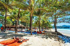 Turister som solbadar på sanden av en tropisk strand i skuggan Arkivfoto