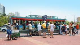 Turister som stiger ombord en Chiva för, turnerar till och med den historiska mitten av Cartagena Fotografering för Bildbyråer