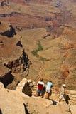 Turister som stirrar på den majestätiska Grand Canyon royaltyfri bild