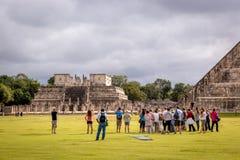 Turister som tycker om en molnig morgon i Chichen Itza nära Cancun i Mexico Royaltyfri Bild