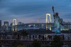 Turister som tycker om sikt av den japanska statyn av frihet och regnbågebron på den blåa timmen royaltyfri bild
