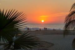 Turister som tycker om solnedgången i Puerto Escondido Royaltyfri Bild