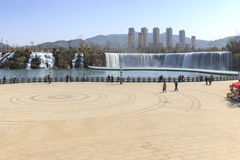 Turister som wisiting den Kunming vattenfallet, parkerar att presentera 400 meter en bred manmade vattenfall Kunming är Yunnans h Arkivfoto