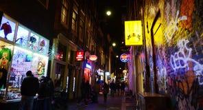 Turister, stänger och coffee shop mycket av på gatan, i rött ljusområde, Amsterdam Arkivbild