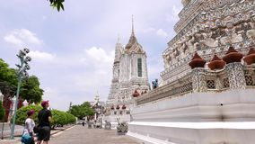 Turister studerar dekorerade väggar och torn den buddistiska templet, Wat Arun, Bangkok arkivfilmer