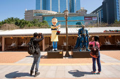 Turister tar bilder av asiatiska tecknad filmtecken i staden parkerar Arkivbild