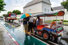 Turister tar den Tuk Tuk servicen i den regniga dagen för lopp på Juli 02, 2015 i Bangkok, Thailand Arkivfoton