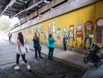 Turister tar foto framme av gatagrafitti under södra förbud Arkivbilder