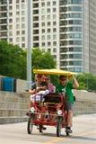 Turister trampar den Four-Wheeled cirkuleringen runt om Chicago royaltyfri bild