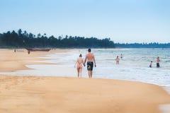 Turister tycker om att gå och att simma på den Hikkaduwa stranden Arkivfoto