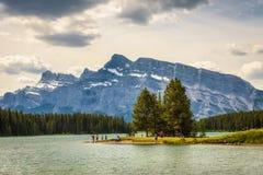 Turister tycker om en solig dag på sjön för två stålar i den Banff nationalparken Royaltyfri Bild